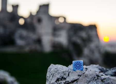 randomness: weather dice with sun sketch on castle background - stock photo Stock Photo
