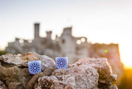 weather dice with sun sketch on castle background - stock photo Stock Photo