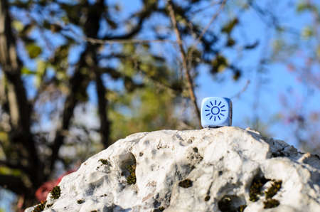 weather dice lying on the rock with sun sketch on nature background - stock photo