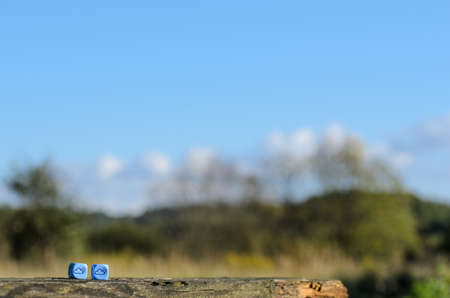 randomness: weather dice with cloud-sun sketch on nature background - stock photo