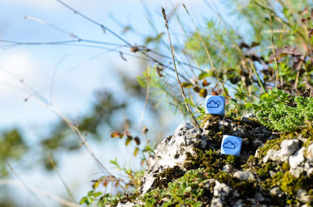randomness: weather dice with cloud-sun sketch lying on the rock on nature background - stock photo