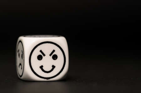 variability: single emoticon dice with happy expression sketch on black background - stock photo Stock Photo