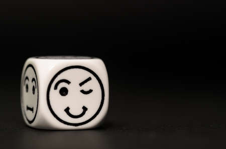 variability: single emoticon dice with blinking expression sketch on black background - stock photo