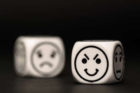 variability: emoticon dice with cunning and sad expression sketch on black background - stock photo