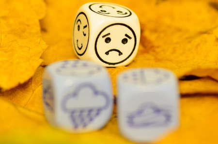 depressing and sad weather of autumn shown on dice weather lying on yellow leaves  - rain and fog - stock photo