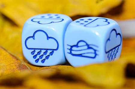 weather of autumn shown on dice weather lying on yellow leaves  - rain and fog - stock photo Stock Photo