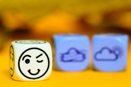 concept of autumn weather - emoticon and weather dice on orange blackground - stock photo