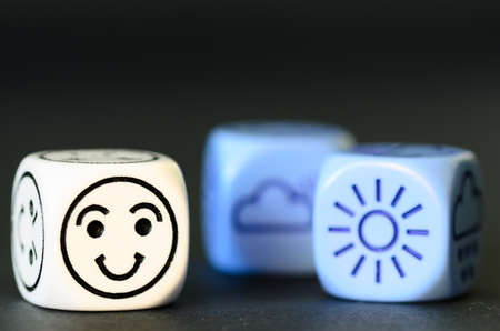 randomness: concept of good  summer weather - emoticon and weather dice on black background - stock photo