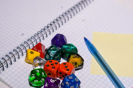 open exercise book with sticky card, pen and role playing dices - stock photo photo