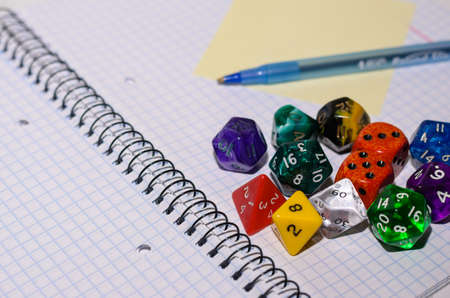open exercise book with sticky card, pen and role playing dices - stock photo
