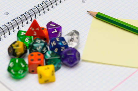 open exercise book with sticky card, pencil and role playing dices - stock photo