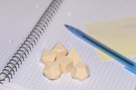 open exercise book with sticky card, pen and rpg blank dices - stock photo photo