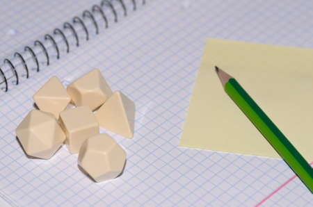 open exercise book with sticky card, pencil and blank rpg dices - stock photo