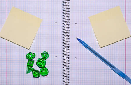 role playing: open exercise book with sticky card, pen and role playing dices - stock photo