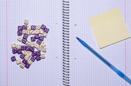 open exercise book with sticky card, pen and dices - stock photo