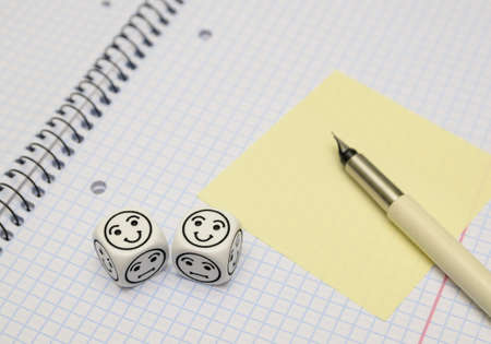 randomness: open exercise book with mood dice (happy) and yellow sticky card - stock photo Stock Photo