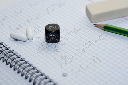 tiresome: study place with painkillers in background and skull dice - stock photo