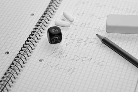 painkillers: study place with painkillers in background and skull dice - stock photo