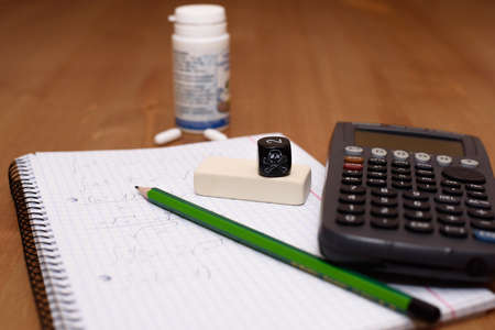 painkillers: study place with calculator and painkillers in background