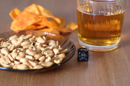 unhealthy snacks on table with skull dice - stock photo photo