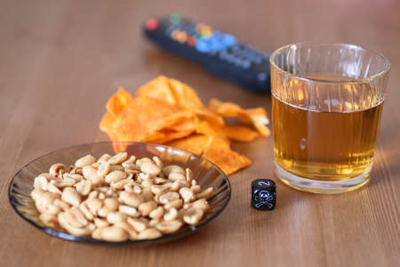 unhealthy snacks on table with skull dice and tv remote  stock photo photo