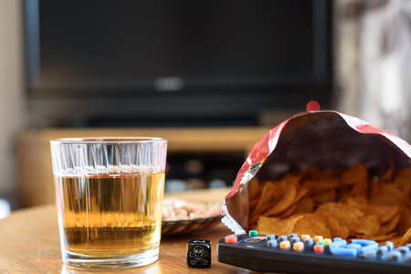 unhealthy food on table with skull dice and tv in background  photo