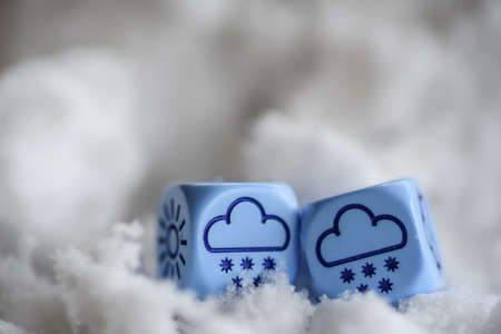 randomness: concept of winter weather, dice with clouds and snow lying on snow - stock photo
