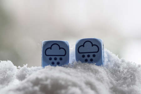 concept of winter weather, dice with clouds and snow lying on snow - stock photo