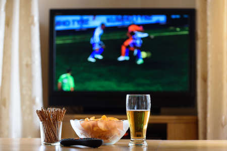 television, TV watching (football, soccer match) with snacks lying on table - stock photo
