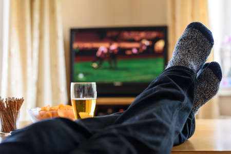 fast foot: Television, TV watching (football match) with feet on table and huge amounts of snacks - stock photo
