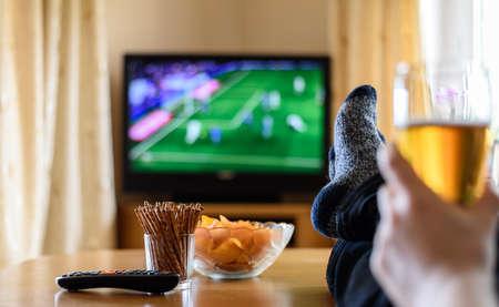 Televisie, tv kijken (voetbalwedstrijd) met voeten op tafel en enorme hoeveelheden snacks - Stockfoto