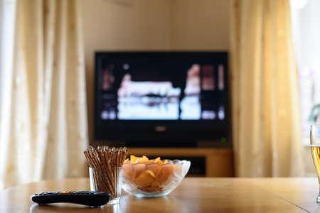 viendo television: televisión, ver la televisión (película) con aperitivos extiende sobre la mesa - foto