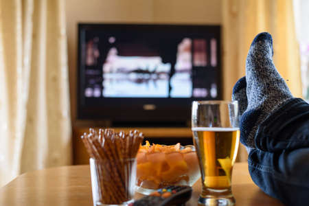 people watching tv: Television, TV watching (movie) with feet on table and huge amounts of snacks - stock photo
