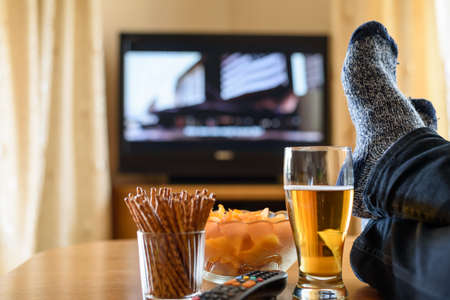 unhealthy living: Television, TV watching (movie) with feet on table and huge amounts of snacks - stock photo
