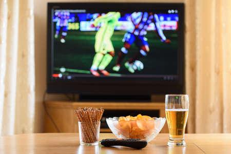 テレビ、テレビ テーブル - ストック フォトの上に横たわるスナック (サッカー、サッカーの試合) を見て 写真素材
