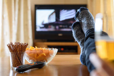 chips: Television, TV watching (movie) with feet on table and huge amounts of snacks - stock photo