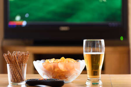leisure game: television, TV watching (football, soccer match) with snacks lying on table - stock photo
