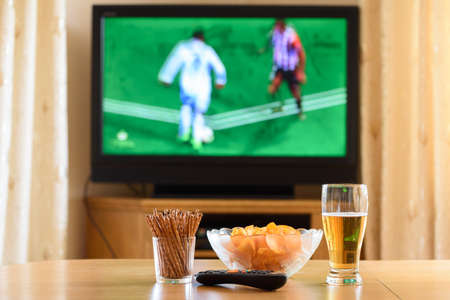 television: television, TV watching (football, soccer match) with snacks lying on table - stock photo