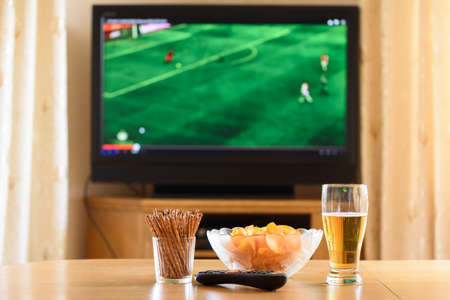 unhealthy living: television, TV watching (football, soccer match) with snacks lying on table - stock photo
