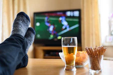 streichholz: Fernseher, TV beobachten (Fußballspiel) mit Füße auf dem Tisch und riesige Mengen an Snacks - Lizenzfreies Foto