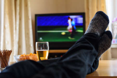 watching football: Television, TV watching (football match) with feet on table and huge amounts of snacks - stock photo