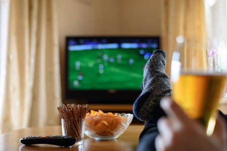 quick snack: Television, TV watching (football match) with feet on table and huge amounts of snacks - stock photo