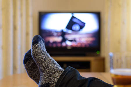 to rebel: TV, television watching (a rebel with isis flag) with feet on the table - stock photo