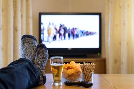 テレビ、スナックを食べるテーブルに足で (難民についてのニュース) を見て 写真素材