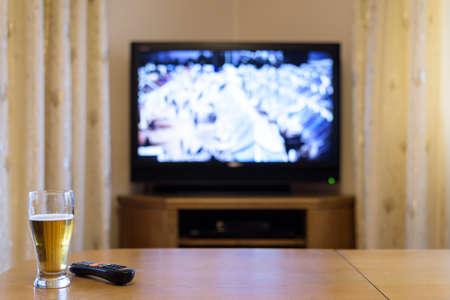 viendo television: TV, ver la televisión (campamento de refugiados) con la cerveza en la mesa