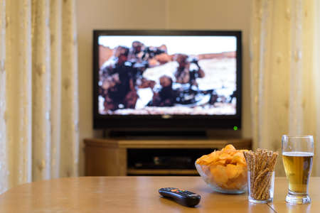 near beer: TV, television watching (american troops, war movie) with snacks lying on the table - stock photo