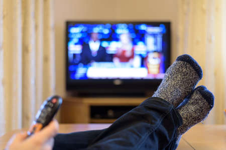 breaking free: TV, television watching (news) with feet on the table and remote in hand - stock photo