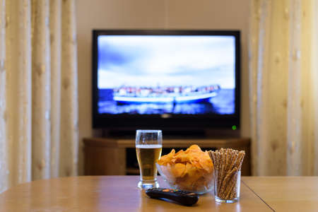 TV, television watching (refugee boat, news) with snacks - stock photo Stock Photo