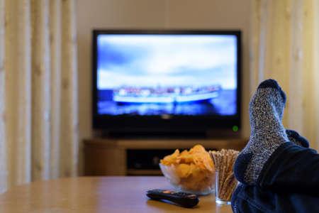TV, televisie kijken (boot met mensen) met voeten op tafel eten van snacks Stockfoto