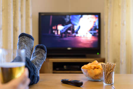 action movie: TV, television watching (boat with people) with feet on table eating snacks and drinking beer Stock Photo